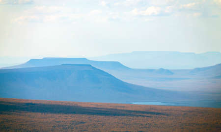 View of the distant typical mountains of the Putorana plateau from a helicopter. Autumn landscape of northern nature in the foothills of the Putorana plateau, top view.
