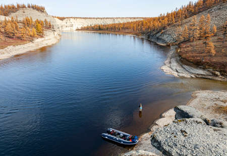 Fisherman with a boat near the shore on the Siberian river in autumn. September landscape on the northern river with clear water. 스톡 콘텐츠