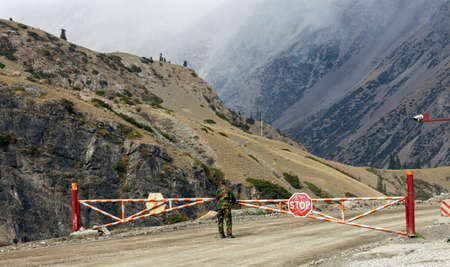 Environmental control barrier on the highway to the mountains. A turning barrier with a STOP sign on a road in a mountainous area.