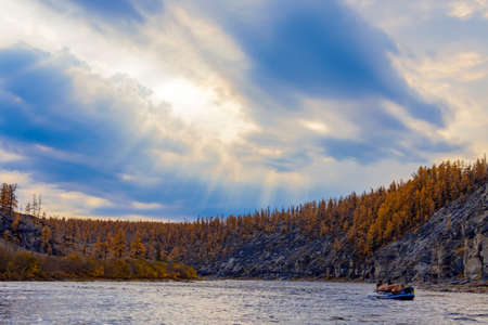 Heavenly landscape with sun rays over the autumn taiga river. A thundercloud over the Siberian riverbed in September. 스톡 콘텐츠