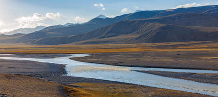 Landscape with road on wide floodplain of mountain river. Panorama with road along the riverbed and mountain steppes at an altitude of more than 3000 meters in autumn in Asia. 스톡 콘텐츠