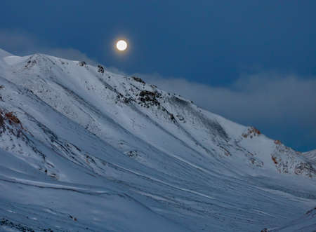 Landscape with full and bright moon over the mountains after snowfall. View of snow-covered mountainside at night under full moon. 스톡 콘텐츠
