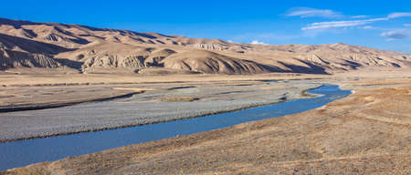 Landscape with view of wide floodplain of mountain river. Panorama with riverbed and mountain steppes at an altitude of more than 3000 meters in autumn in Asia.