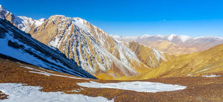 Panorama of the mountainous terrain from the top point of the pass. Rocky cliffs and snow-covered slopes of the Asian mountains in early winter. 스톡 콘텐츠