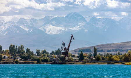 Port cranes of the Przhevalsk pier on the Issyk-Kul lake on the background of mountains. Landscape of the eastern shore of Lake Issyk-Kul from the water. 스톡 콘텐츠