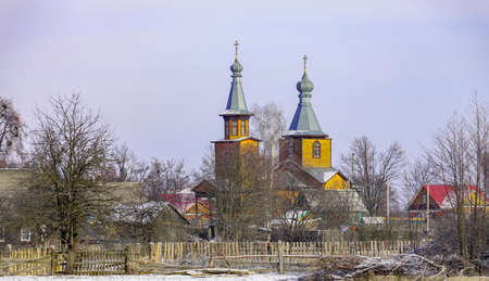 View of the outskirts of a Belarusian village in January after a morning snowfall. Landscape from the edge of the village of Lyaskovichi and St. Michael's Church on a winter frosty day.