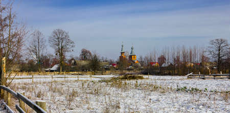 Landscape on the outskirts of Belarusian village in January after a morning snowfall. View of the village of Lyaskovichi and St. Michael's Church on a frosty winter day.