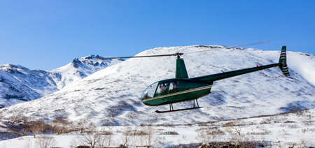 Green helicopter with masked passengers flies over a mountainous area. Small helicopter in flight against the background of snow-capped mountains and blue sky. Kamchatka.