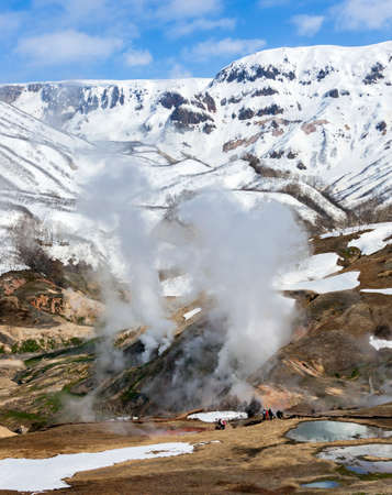 Ecological trail with tourists on the background of vapors and gases of the Valley of Geysers. Landscape of the Valley of Geysers with group of tourists on the route in the Kronotsky Nature Reserve in Kamchatka.