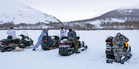 Men in camouflage winter suits inspect the surrounding mountains from snowmobiles with binoculars. Five hunters are searching for animals in a snow-covered area. Kamchatka.
