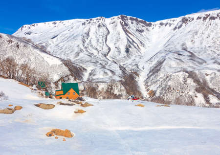 White helicopter is landing at house with green roof in mountainous snow-covered area. Building of the cordon with helicopter pad in the landscape of the Valley of Geysers of the Kronotsky Reserve in Kamchatka.