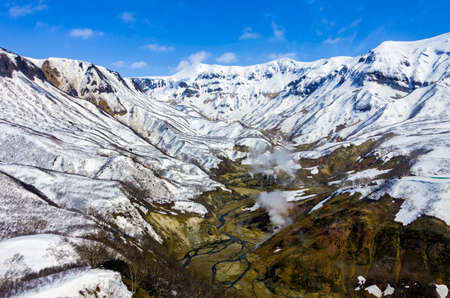 Top view of the snow-covered Valley of Geysers in May after a snowfall. Steam and gases from geysers and hot springs in the active part of volcanic activity. 스톡 콘텐츠
