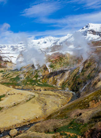 Spring landscape with columns of steam and gases in the Valley of Geysers. Active volcanic activity and thermal fields in the floodplain of the Geysernaya River in Kamchatka.