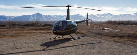 Small helicopter is parked on a dirt platform against the backdrop of mountains. A passenger pleasure helicopter on a landing pad in a flat area.