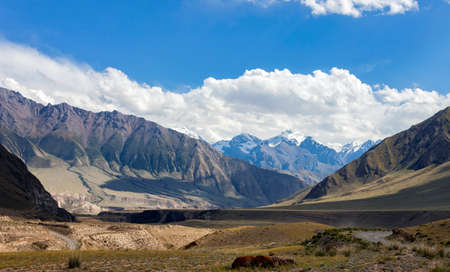 View of the mountain valley and steppe pastures in the spurs of the Tien Shan. A typical sky landscape and a dirt road along the floodplain of mountain river.