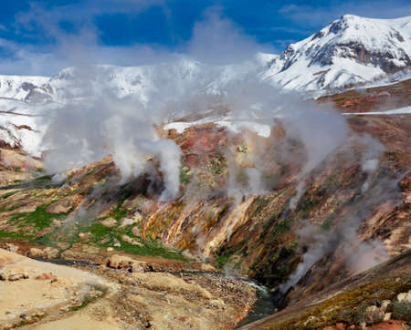 May landscape with columns of steam and gases in the Valley of Geysers. Active volcanic activity and thermal fields in the floodplain of the Geysernaya River in Kamchatka.