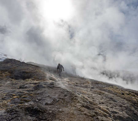 Tourists climb the side of the volcano in clouds of hot steam and gas emissions.Hot steam and gas demonstrate volcanic activity in spring in Kamchatka.