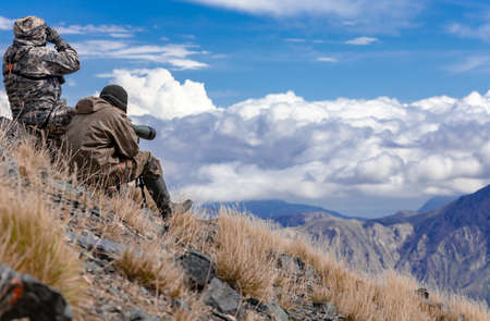 Two men in camouflage on the slope are watching in the optics in the mountains. Hunters look through binoculars and a telescope against the background of the sky and mountain landscape.