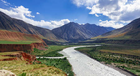 View of mountain valley with river and steppe pastures in the spurs of the Tien Shan. A typical sky landscape above the floodplain of mountain river with a right tributary.