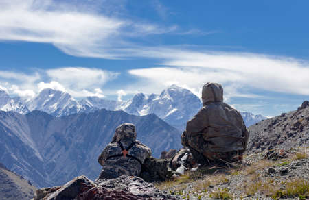 Two men in camouflage suits are conducting surveillance at the top of the mountain. Hunters with weapons in protective clothing with binoculars are searching for mountain animals. 스톡 콘텐츠