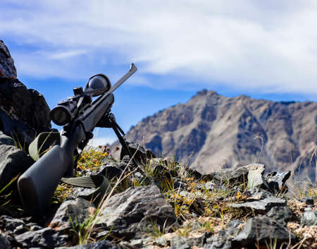Rifle with a telescopic sight on a bipod before shooting in the mountains. Hunting weapons with optics for long-range shooting while hunting in the mountains against the sky.
