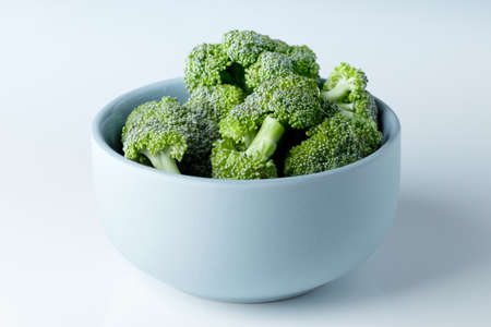 fresh slices of broccoli in a light blue and dull ceramic bowl on white background, soft light and shadows, lookin from the side into the bowl Archivio Fotografico