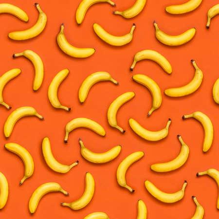 seamless banana pattern with random oriented banana fruits on orange background, repeatable pattern texture Foto de archivo