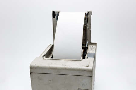 Open receipt printer for exchanging the thermal paper roll, old and used printer on white isolated background with dirt and grunge, connected to a cash register