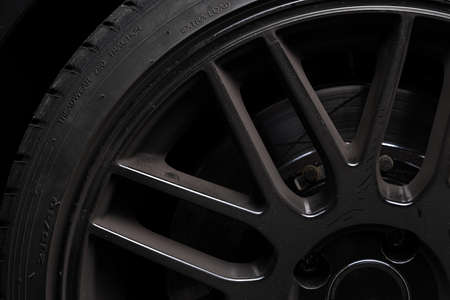 Side view of a black aluminum rim with rubber tire, dirty, dusty, break dust, picture shows a low key shot of a rim on dark black background.