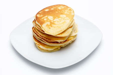 High angle view of a stack of pancakes on a white plate on white uniform background, typical American breakfast food