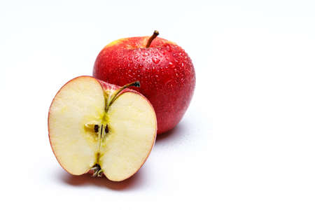 two red apples with water splashes on a white uniform background, one apple is cut in half looking onto the fruit stem and seeds. Stok Fotoğraf