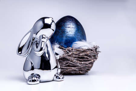 Cute silver metallic easter bunny figure looks onto a royal blue easter egg laying in a easter nest made of brown branches, filled with white feathers on white uniform background Stok Fotoğraf