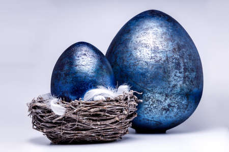 Two royal blue easter eggs in different sizes on a white and uniform background, one egg is in a easter nest with some white and fluffy feathers, popular easter decoration