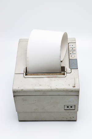 Top view of an electronic recipe printer with paper roll, old and used printer on white isolated background with dirt and grunge, connected to a cash register