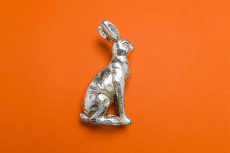 Side view of a silver metallic easter bunny figure on a red uniform background with light soft shadows, use as easter virtual meeting background.