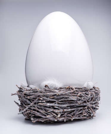 one large ceramic easter egg in brown gray easter nest with white feathers, creative easter and spring decoration 2021, trend colors on white isolated background