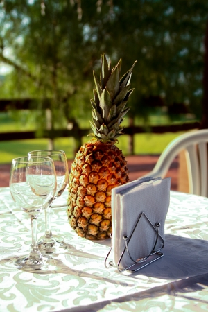 Two wine glasses and pineapple on the served table at sunset photo