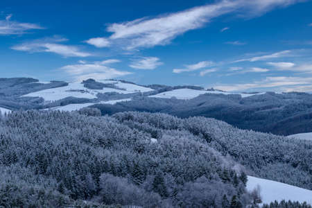 Color winter panorama of a snowy countryside with trees, forest, hills, farm buildings, fields, valleys and a view towards the horizon under a blue sunny sky with some clouds