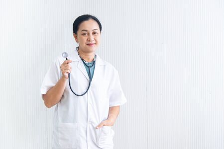 Portrait confident and smiling woman doctor with white uniform and the stethoscope (medical device) on white blackground  at the hospital or clinic, Asian female doctor in medical gown, healthcare business