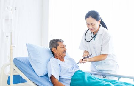Asian woman professional doctor with clipboard visiting and diagnosing the old man patient lying in bed at hospital ward. Physician has a routine work to check up and have consulation the patient