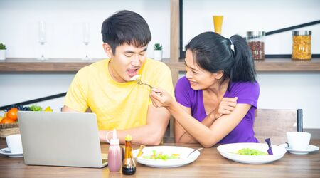 Happy and funny family. Asian lovely couple, beautiful woman and handsome man is having American breakfast, drinking coffee, talking and working together in the kitchen