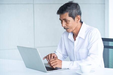Un vieil homme d'affaires asiatique aux cheveux blancs, à la chemise et à l'ordinateur portable travaille, réfléchit, planifie dans la salle de réunion du bureau moderne sur l'avenir de l'entreprise comment réussir et éviter l'échec