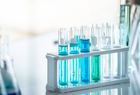 Preparing Laboratory equipments such as glassware, tube with blue liquid on the white table. The chemistry experiment in scientific research Stock Photo