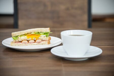 Sandwich and cup of coffee on white plate and wooden table, sandwich is made from bread, sausage, fried egg and vetgetable is American breakfast or fast food is unhealthy food or junk food Stock Photo