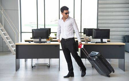 Young and smart businessman with sunglasses, suitcase and travel document such as air ticket, hotel booking document and passport with travel concept,summer vacation concept, summer holiday concept