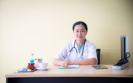 The closed up woman doctor with white uniform  and medical devices such as stethoscope and blood pressure device is checking up the patient health and taking note on the white paper at the hospital or clinic wihic is the healthcare business