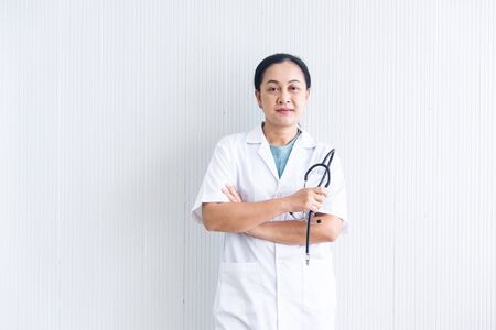 The closed up confident and smiling woman doctor with white uniform and the stethoscope (medical device) on white blackground  at the hospital or clinic, Asian female doctor in medical gown, healthcare business Imagens