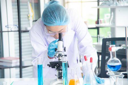 Scienziato, ricercatore, tecnico o studente asiatico ha condotto ricerche o esperimenti utilizzando il microscopio che è un'attrezzatura scientifica in un laboratorio medico, chimico o biologico Archivio Fotografico