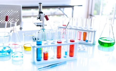 Preparing Laboratory equipments such as glassware, tube with blue and liquid on the white table. The chemistry experiment in scientific research