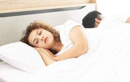 Family relationship problem concept.  Couple lying in bed under white blanket.  Lover concept.  Caucasian beautiful woman with blonde hair worried about the relationship with Asian handsome man sleeping on bed Stock fotó